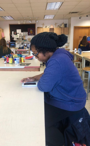 NAHS member and senior Destiny Hall looks at art-themed parties on her phone to brainstorm ideas with her fellow committee members.