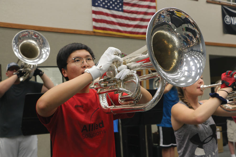 Noah Sim, marching band member and senior, rehearses on his euphonium during summer marching band rehearsals. Sim began to play the euphonium for marching a year ago. Sim said the summer rehearsals allow for the marching band to get a head start, as well as integrate freshmen with upperclassmen.