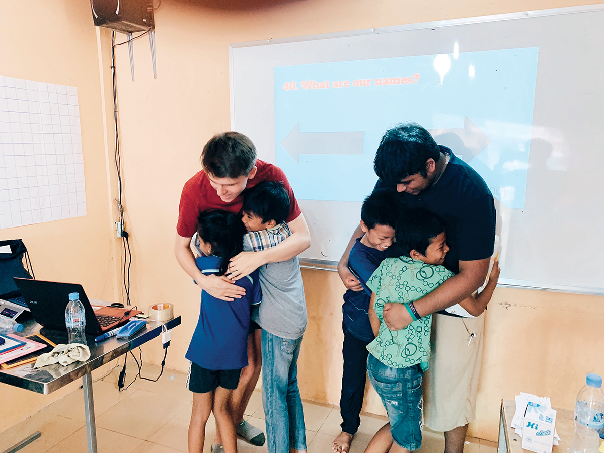 """Senior William """"Will"""" Pugh (left) hugs two Cambodian students. Pugh said his involvement in the TASSEL club to help others has had a positive influence on him."""