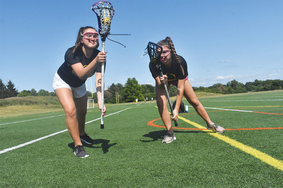 PARTNER IN CRIME: (LEFT) Juniors Gretchen and Anna Moore practice Lacrosse together over the summer. Anna said there are moments when they wish they weren't, but they also couldn't imagine living without each other. Anna also said her favorite part of being a twin is always having someone to talk to and never having to go to social events alone.
