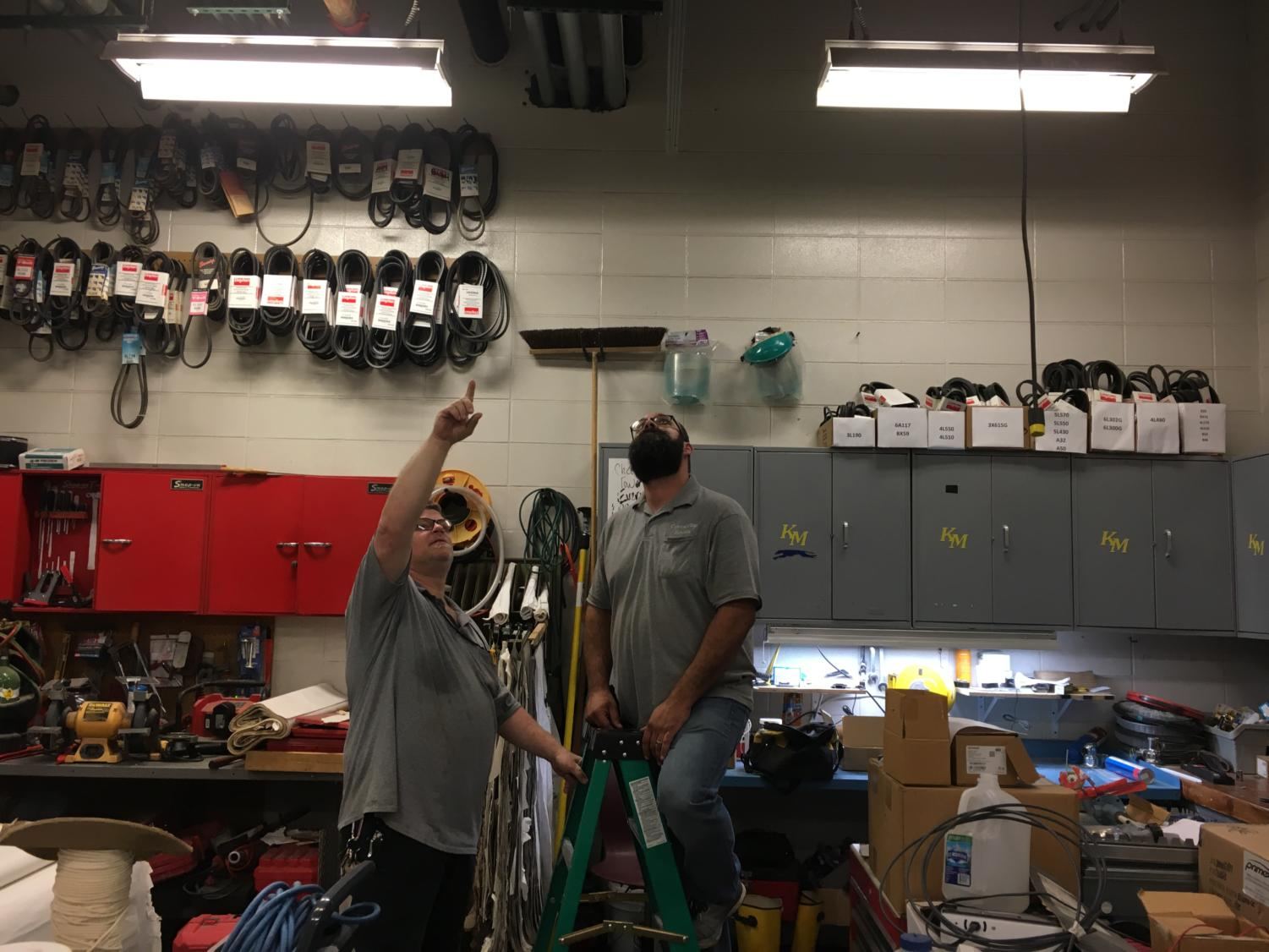 Maintenance worker Fred Napier holds the ladder for another maintenance worker as they fix a light that has gone out in the maintenance shop. This is the same kind of thing they do when teachers submit work orders.
