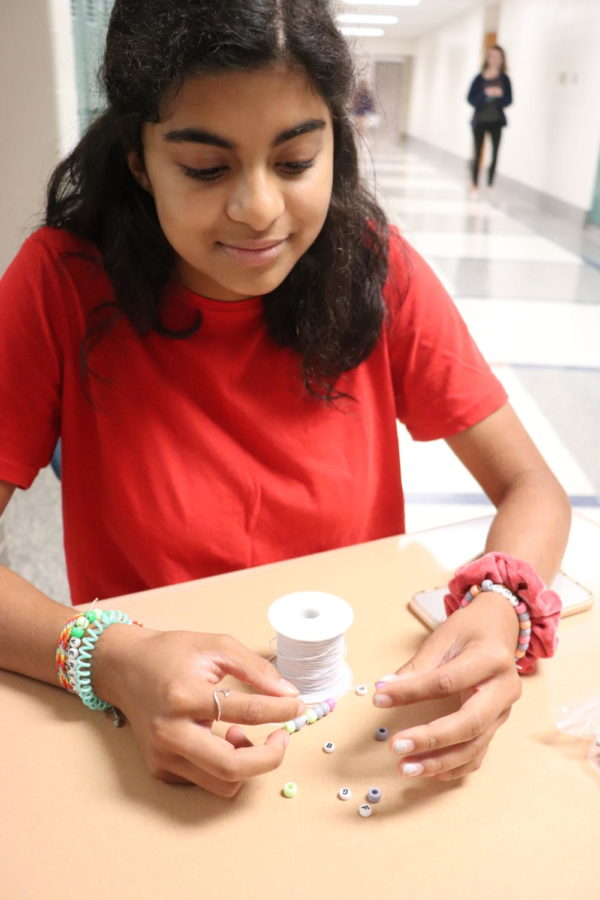 BEAD IMPACT: Sophomore Varsha Chan- dramouli makes a bracelet out of letter beads. Over the sum- mer, she started making and selling these bracelets on Instagram to raise money for the Marine Conservation Institute.