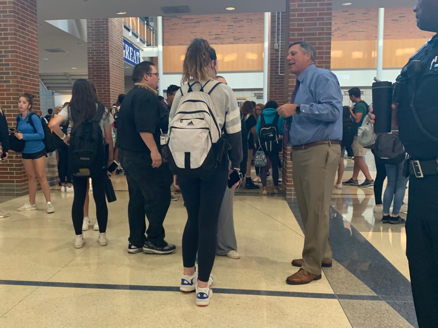 Principal Tom Harmas converses with students in the hallway during a passing period. He said he's excited to see all the homecoming changes in action and how the student body reacts to them.