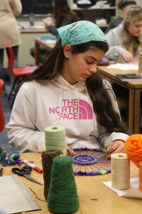 FIBER ARTS FUN: Hannah Nazzal, fiber arts student and junior, works on a weave during her G3 fiber arts class with Mrs. Palmer on Feb 27. Students interested in fiber arts can join the Fiber Arts Club that meets in room C129 after school on gold Wednesdays.