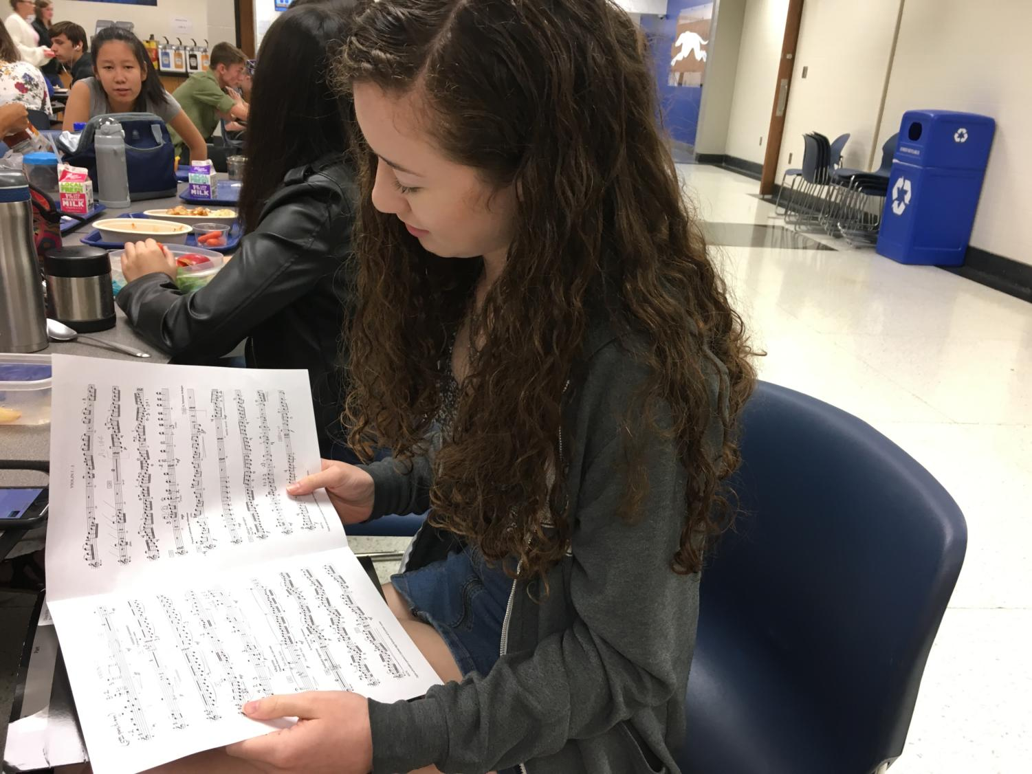 Olivia White, Philharmonic Orchestra member and junior, looks over her concert music. White said she has been recording herself practicing the music to keep track of her progress and use different practice techniques.