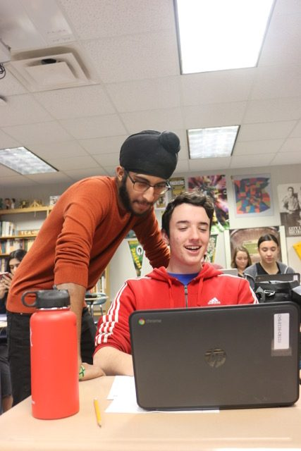 REVISION REVELRY: Junior Wiliam Van Horn (right) shows junior Sumeet Singh (left) his assignment on a class activity in their AP Seminar class on Jan 8. This semester the class will redo the same assignments they were assigned as last semester to submit to the College Board as part of their AP exam for the class.