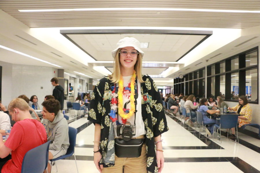 Senior Mallory Hale poses with her tourist day outfit featuring a camera, bucket hat, and Hawaiian garments.
