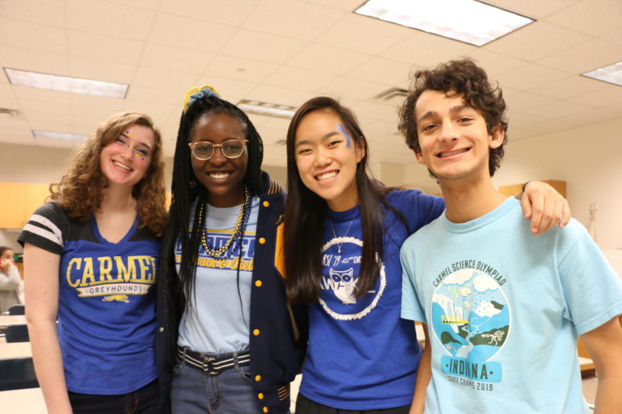 Juniors Sarah Konrad and Urego Agada and seniors Iris Yan and Yannik Singh pose for a photo in their blue shirts for blue and gold day.