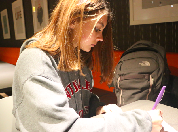 STUDYING HARD: Sophomore Samantha Daugherty studies her bio-med notes for her upcoming final on December 9th. Daugherty explained how she finds the topic interesting and she enjoys to study the material the most in the Carmel Café because of the cozy and quiet atmosphere. Daughtery feels stressed but ready for her upcoming assessments and plans to study in the Café a lot more.