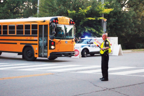 Student Resource Officer Shane VanNatter directs buses and traffic in the morning. VanNatter said a crash could easily occur while the buses are exiting the school.