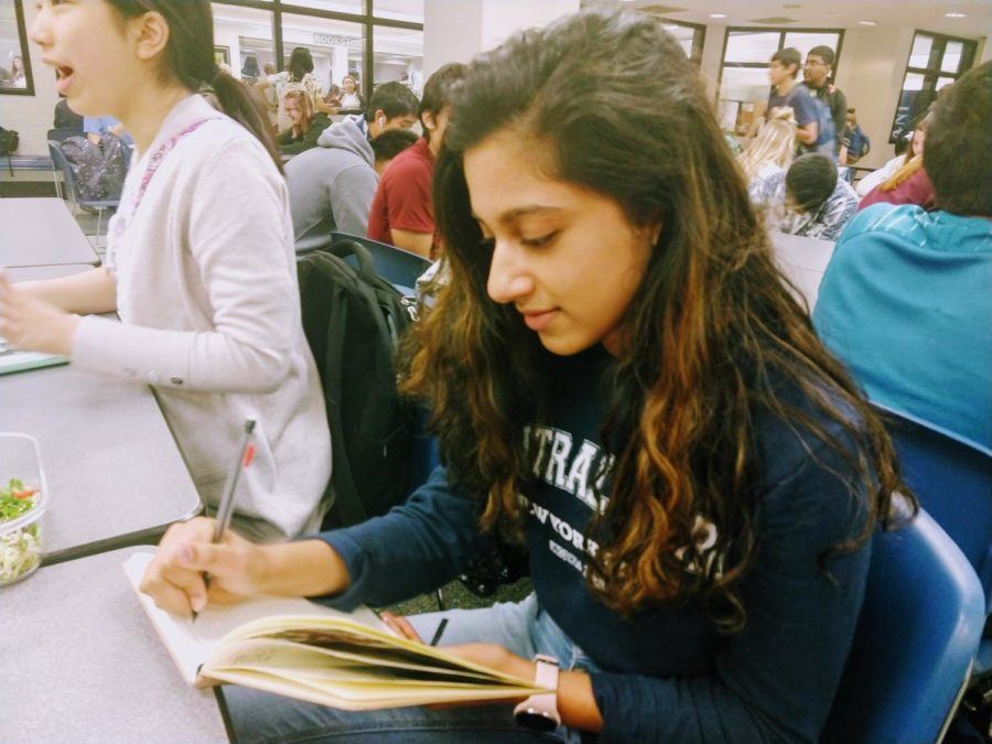Junior Nishita Prasad finishes up her French homework during lunch before heading to class. Prasad said she likes the changes being made to the classes because they have improved her overall understanding of the language.