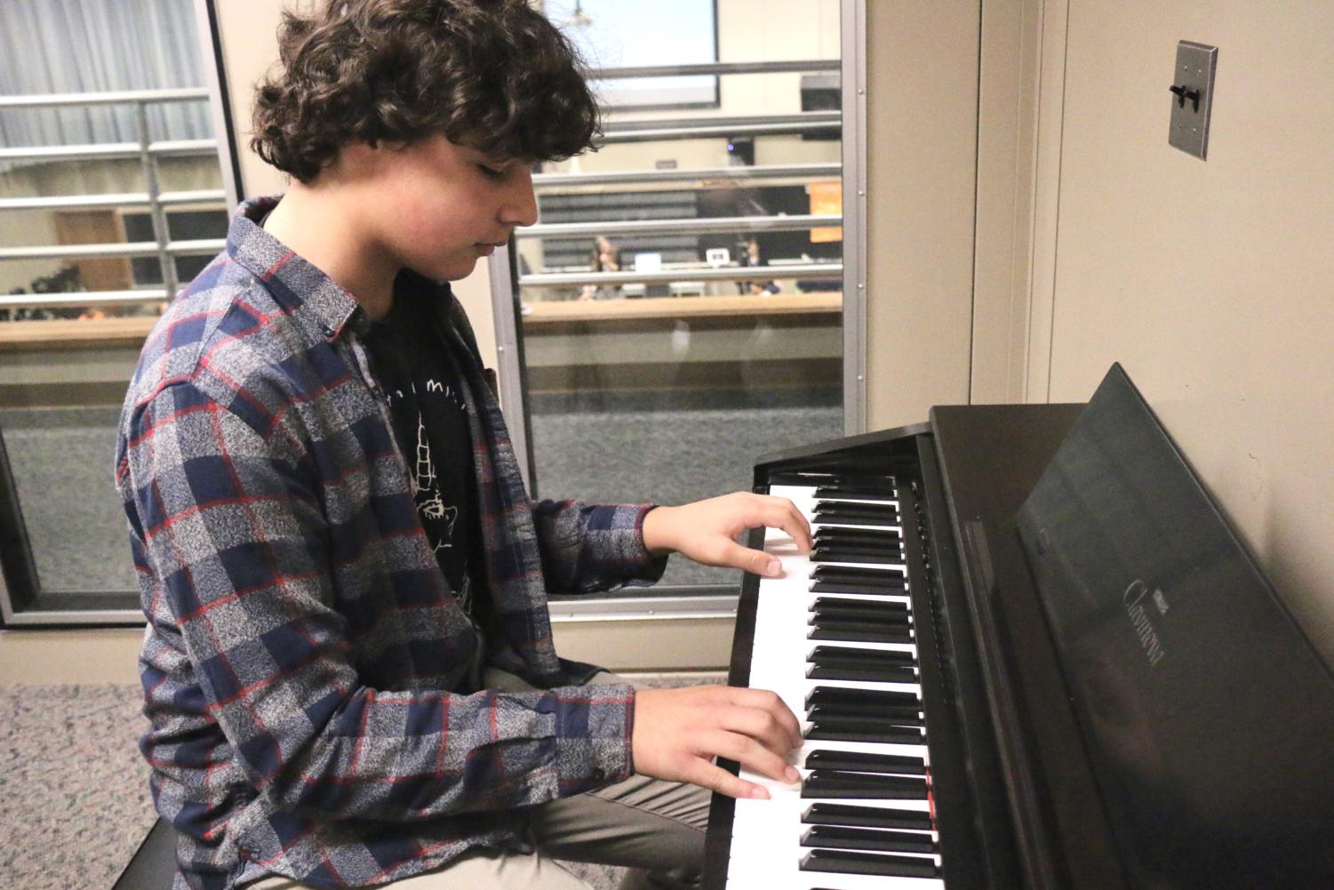 Sophomore+Caleb+Beik+improvises+a+small+tune+while+warming+up+for+a+concert+practice+on+October+3.+Beik+states%2C+%E2%80%9CI%E2%80%99ve+been+playing+piano+since+I+was+three+years+old%2C+it%E2%80%99s+something+that+comes+natural+to+me+at+this+point.+I+love+being+able+to+express+myself+with+music%E2%80%9D.+Beik+explains+when+he+has+free+time+during+class+periods+he+practices+his+skills+during+them.+THEA+BERTOLINI%2FPHOTO.+%0A