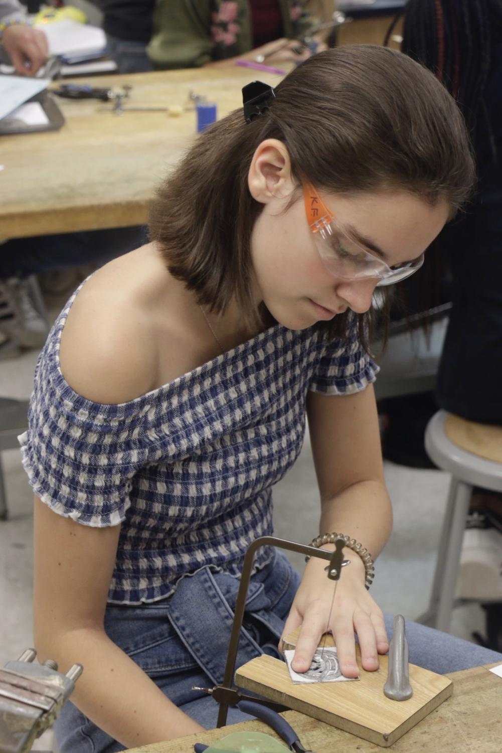 SERIOUS+SAWING%3A+Jewelry+student+and+sophomore+Kendall+Frobig+cuts+her+design+out+of+metal+with+a+saw+frame+in+the+jewelry+classroom+on+Oct.+28.+The+jewelry+piece+is+for+the+Culture+of+Care+week+project%2C+where+students+create+a+piece+to+give+to+someone+who+inspires+them.+Frobig+said%2C+%E2%80%9CMy+take+away+from+this+class+is+that+there+are+so+many+ways+you+can+be+creative%2C+I+never+thought+I%E2%80%99d+be+working+with+metal+and+creating+wearable+pieces%2C+but+here+I+am.%E2%80%9D+