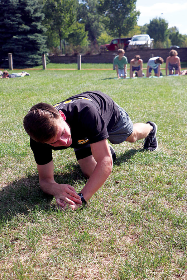 "Logan Sandlin, varsity track and junior varsity cross country member and senior, does exercises during practice. His participation in sports required him to attend the ""Step Up to Sexual Assault"" presentation this year."
