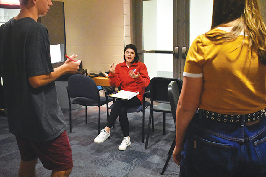 """BEHIND THE SCENES: (ABOVE) Piper Williams, Studio One Acts student director and senior, discusses the show, """"The Rental,"""" with two student actors. Williams said, """"Theatre is always going to be a part of my life, so I'd like to direct a smaller community theatre for sure."""" Studio One Acts will present four separate plays starting on Oct. 5 in the Studio Theater."""