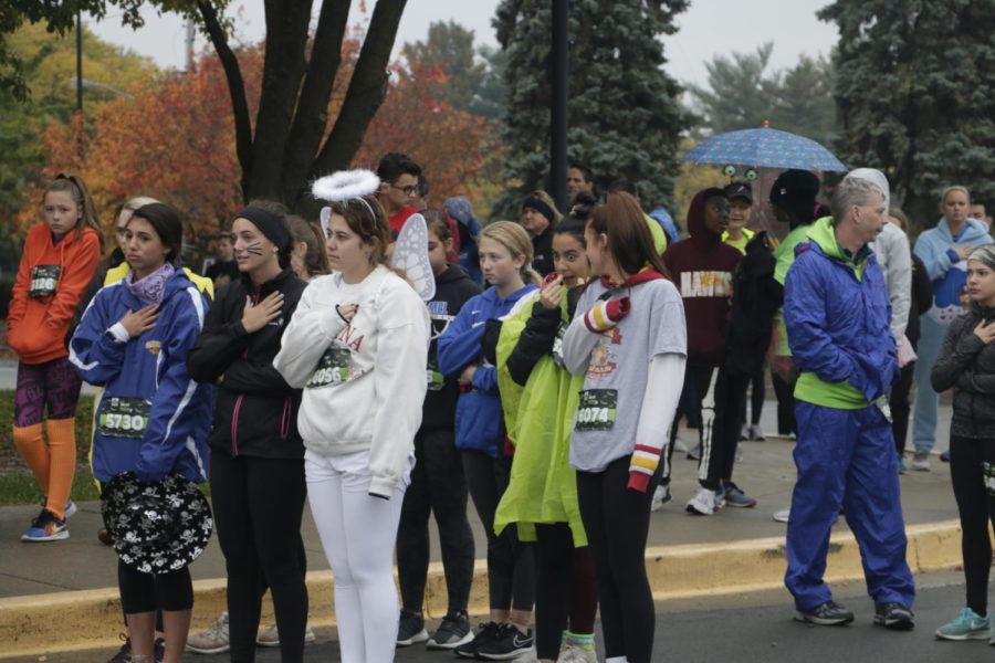 Before lining up for their races, runners listen as the national anthem is sung. Before running, participants are given the opportunity to socialize in the parking lot and take pictures with various mascots.