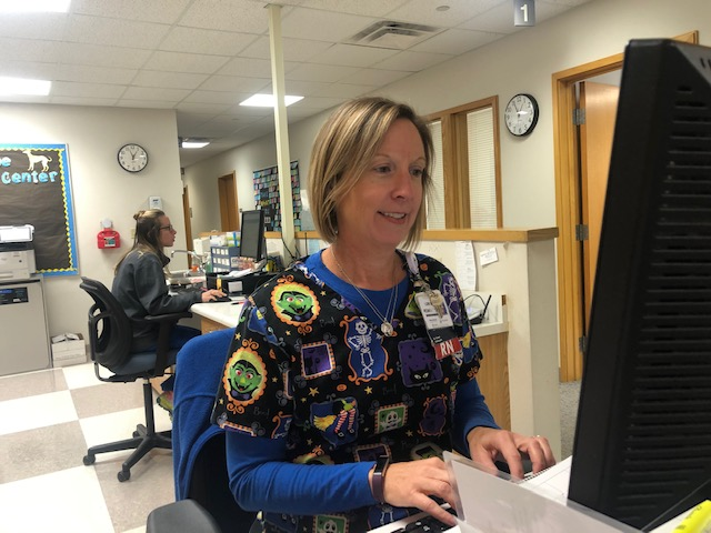RN Lori Baldwin finalizes paperwork on her desktop. Baldwin said she would like to be a friendly face for all students feeling under the weather.