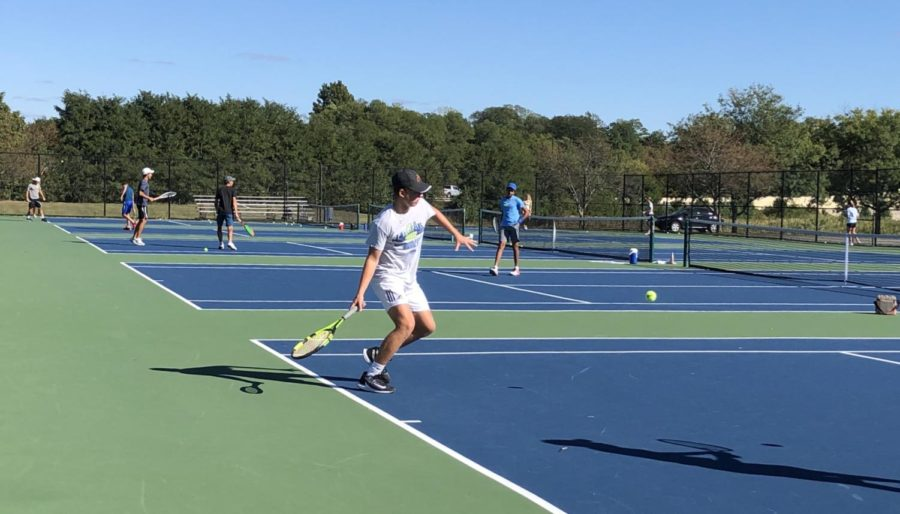 Varsity tennis player Presley Thenieman practices aggressive play for the State competition. He, along with the rest of the varsity team, won both of their matches at Sectionals.