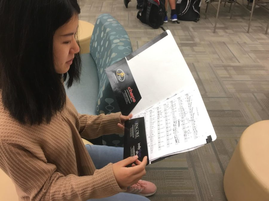 Chloe Chui, member of Symphony Orchestra and junior, looks over her concert music before school. Chui said that in the final weeks before the fall concert, she has been focusing on adding musicality to her pieces and refining her playing.