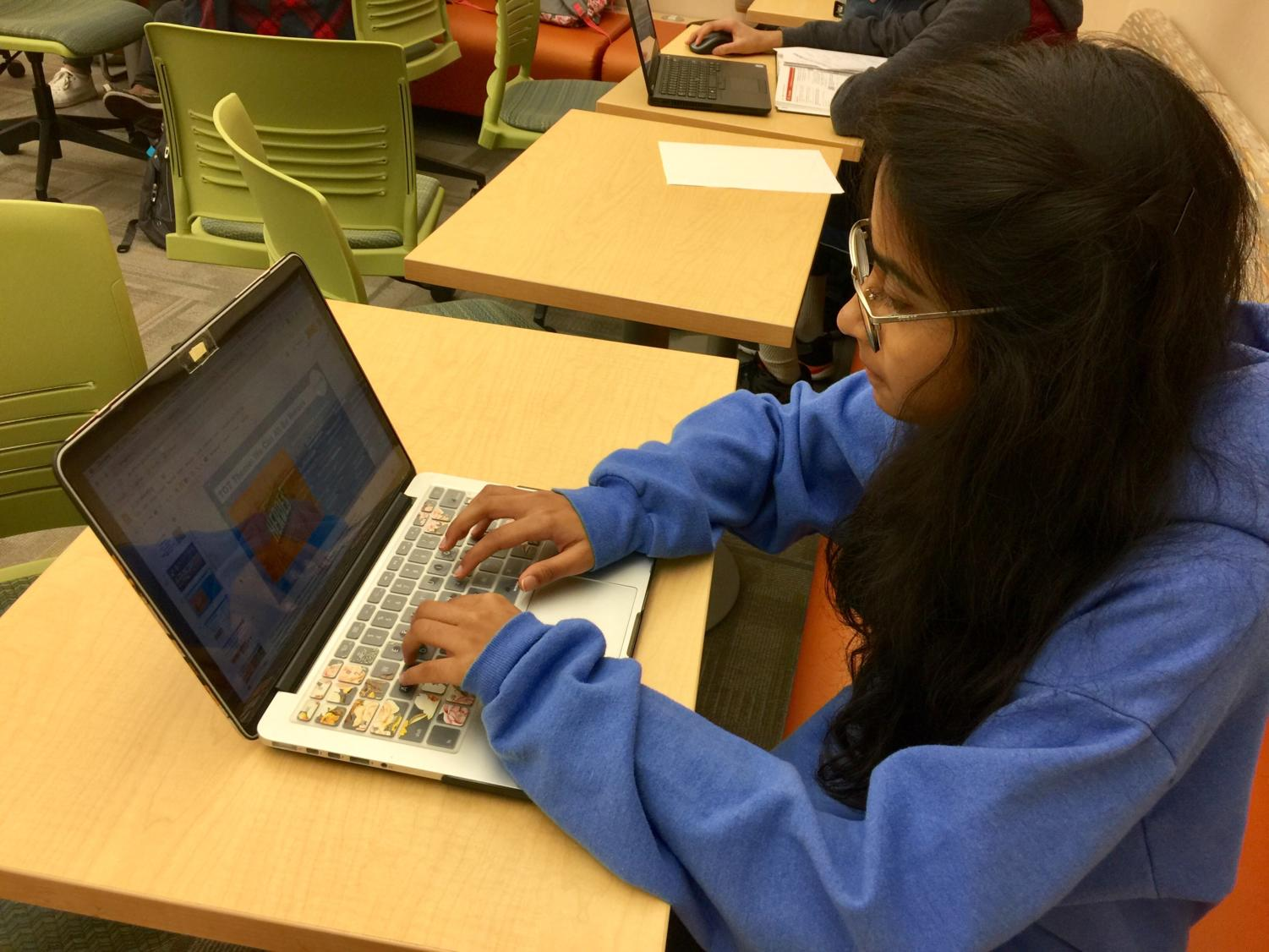 Viha Bynagari, Carmel UNICEF co-president and senior, edits a Carmel UNICEF powerpoint in the media center. She said UNICEF is hosting a Give Back night will take place every Friday in October, and anyone is welcome to volunteer by DM-ing Carmel UNICEF's Instagram.