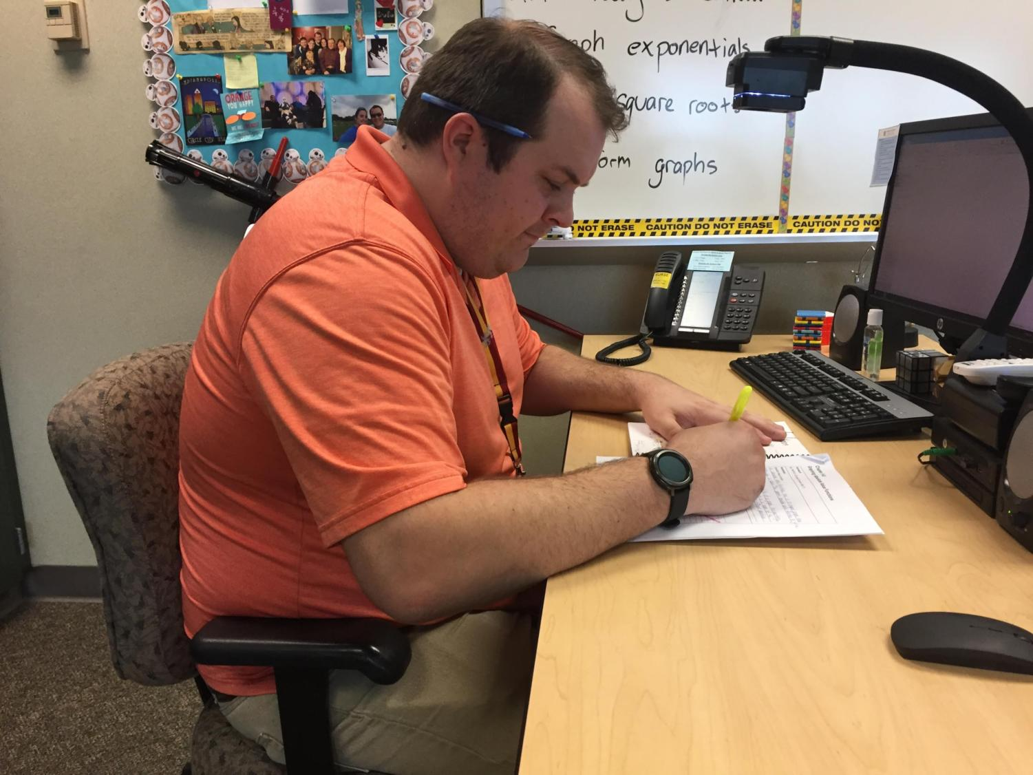 Joseph Broman, sponsor and math teacher, reviews upcoming competitions for Math Club on his computer. Broman said many of the competitions will take place during first semester.