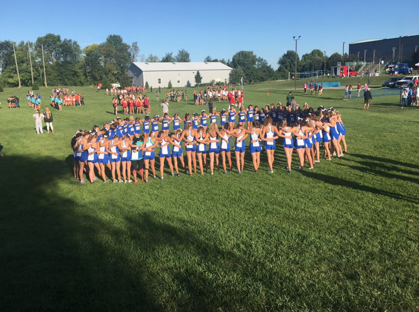 "The varsity team huddles up prior to a home meet. ""We are looking forward to the rest of the season and hopefully can win a State championship this fall,"" varsity runner and senior Phoebe Bates said."