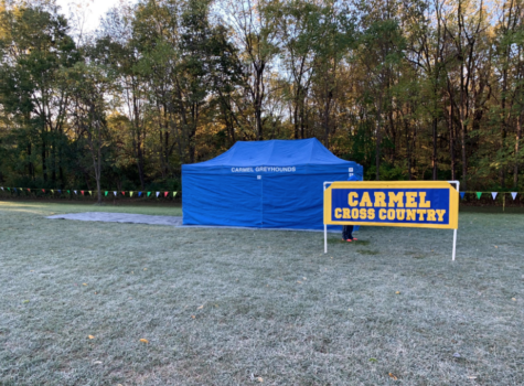 "The cross-country banner and tent get set up prior to a meet. Varsity runner and senior Phoebe Bates said, ""We are hoping to finish the season strong and win another State championship."""