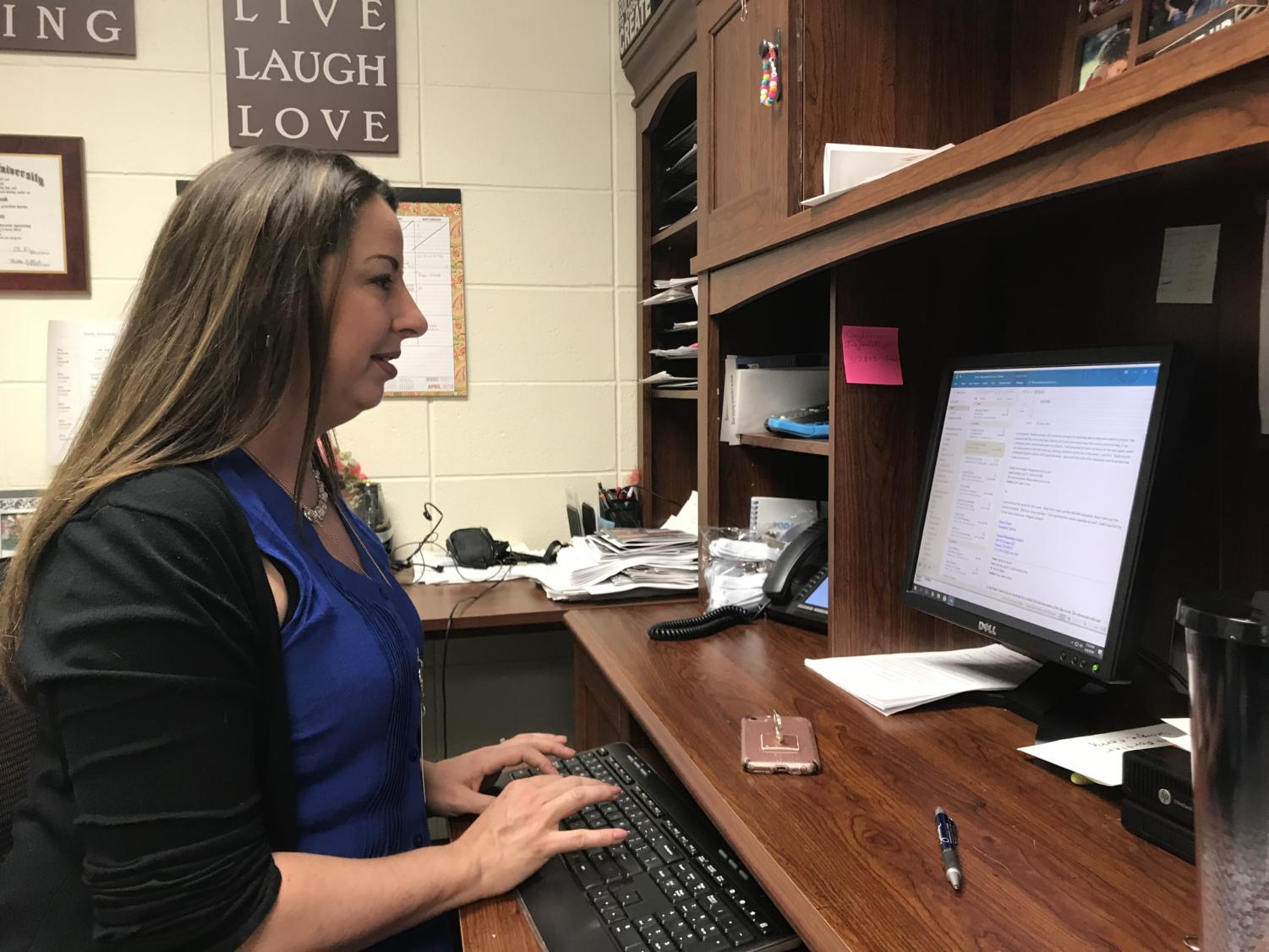 Director of Choirs Katherine Kouns responds to a parent email in her office before school on Oct. 17. The email was in regards to the booster organization that the choirs use, Ovation.