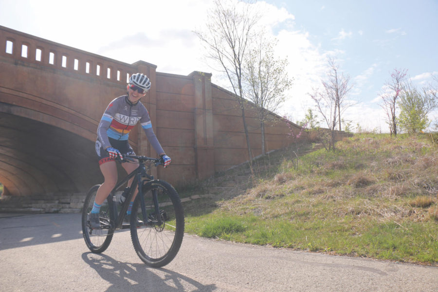 Senior Ellie Dyas rides her bike—cycling can be a team or individual sport. Dyas said she will often cycle in the front during team events so that her teammates behind her conserve energy to win at the end, since aerodynamics play a large factor in fast-paced road cycling.