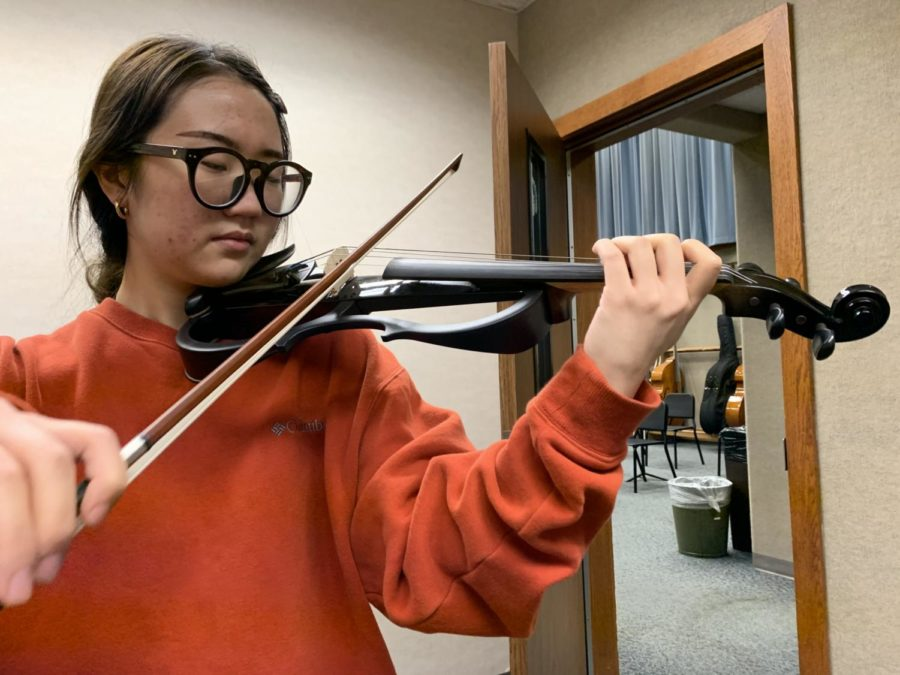 """Playing on the electric violin, Jiwon Yu, the club's president and senior, practices the bowing skills and basics that she strongly advises other members of the Carmel Electric Ensemble to focus on until the first rehearsal and the promo concert set for Dec. 12. Yu said a reminder for the members is to """"bring your bows so we can play."""""""