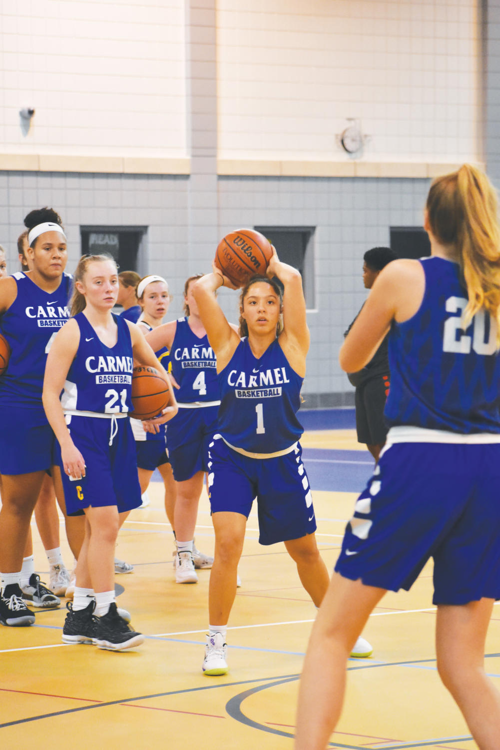 SHOOTAROUND: Senior Kiara Gill passes the ball during a drill as the team looks on. The team opens the season with a long road trip to Homestead.
