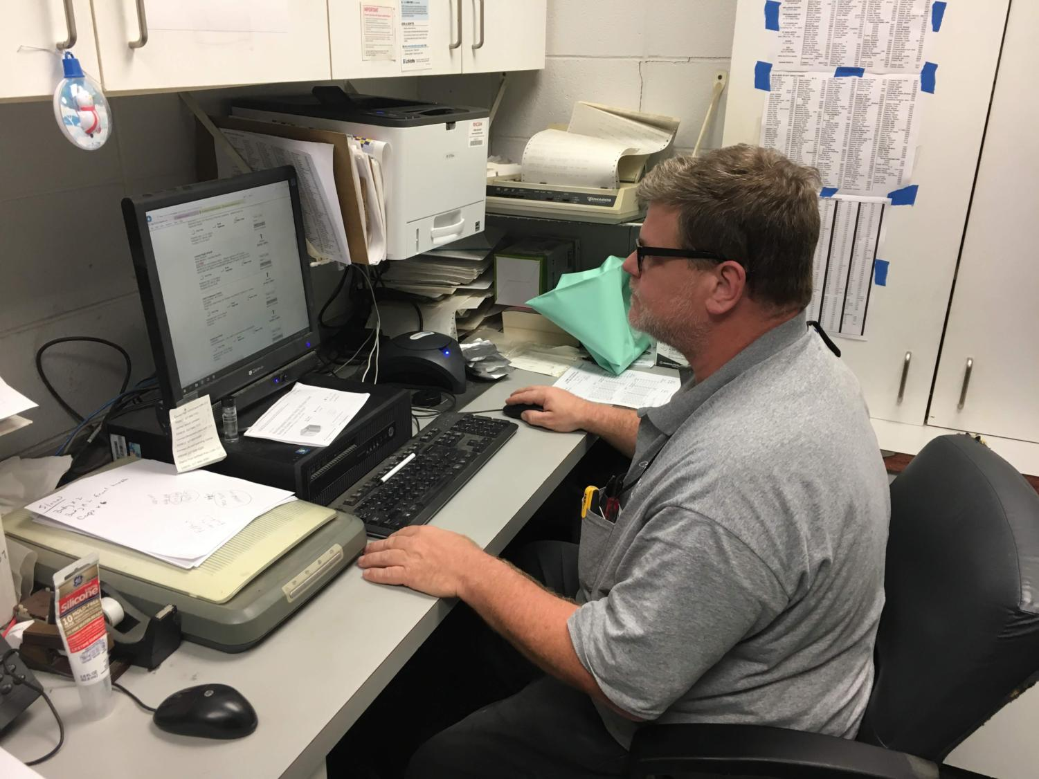 Maintenance worker Fred Napier scrolls through work orders on his computer in the maintenance shop. Napier said that not only does the maintenance staff have to deal with big things like salting parking lots, but they also have to keep up with the day to day needs of the school in the form of work orders.