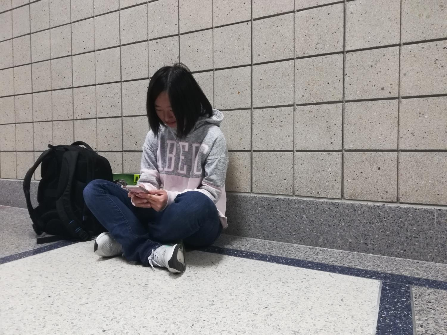 Sophomore Eliana Jin looks at her phone to read the email Melinda Stephan, college and careers programming and resources coordinator, sent out about the upcoming Business Majors and Careers Fair. According to Stephan, the fair will be on Nov. 19 in the Freshman Center cafeteria from 6:30 to 8 p.m.