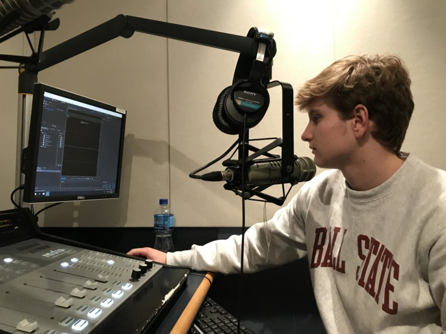 Charlie Maurer, co-sports director and senior, sits in a recording booth.