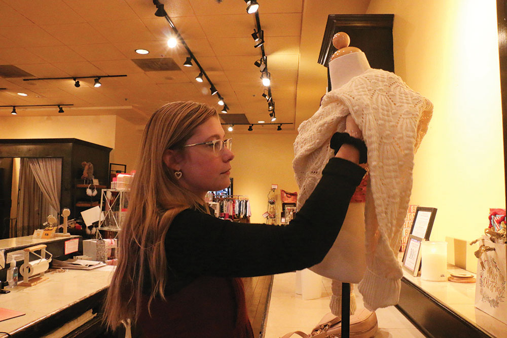 SETTING UP Senior Natalie Crispin sets up a clothing display at Francesca's. Crispin said working on Black Friday was hard because she couldn't take her time helping customers.
