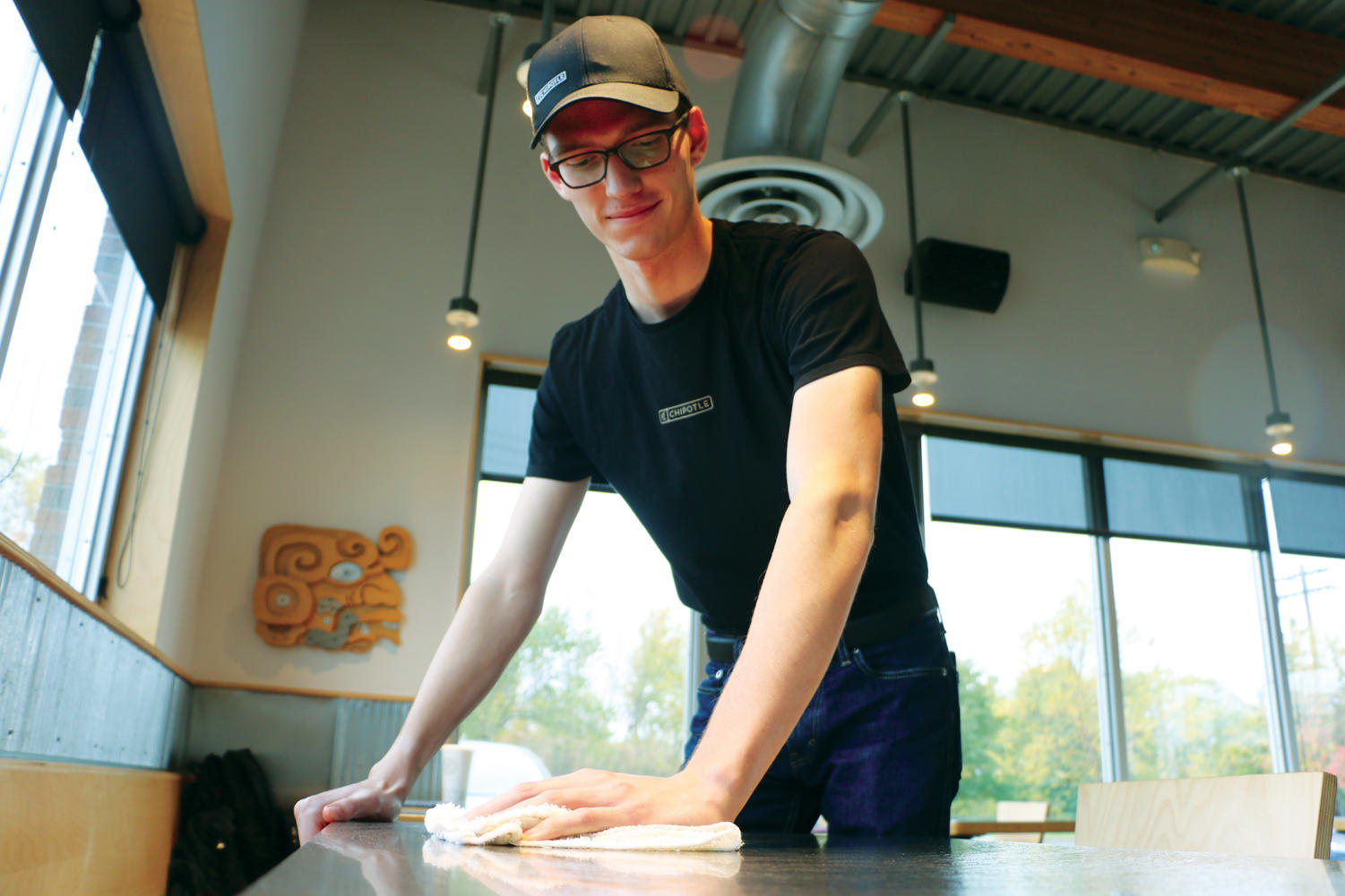 Ben Ring, Chipotle employee and senior, wipes down a table during one of his shifts at Chipotle. Ring said cleaning up is one of the responsibilities he has as a worker for Chipotle.