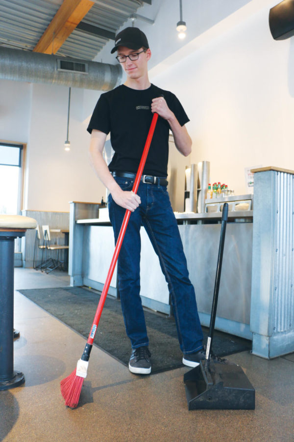 Ben Ring, Chipotle employee and senior, sweeps the floor during his shift. Ring said he enjoys working as he learns many new skills.