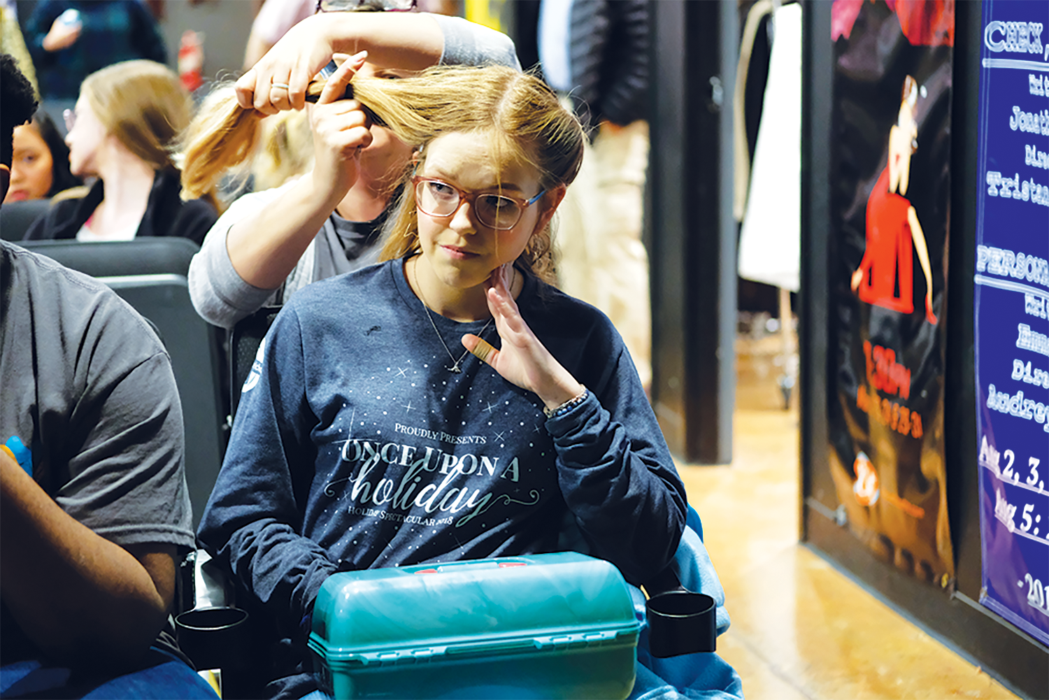 """THE SUN WILL COME OUT: Senior Lydia Rusin listens to advice from a consultant on how to match her makeup to the time period of """"Annie"""" while an adult volunteer helps her put up her hair. Rusin said she decided to join the cast because there were not going to be cuts to the cast list."""