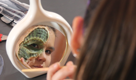 SCALY TRANSFORMATION: Looking in a mirror, junior Lydia Schrader applies green makeup onto a special effects prosthetic to create a scale-like look. Schrader said these green lines create more depth and make the prosthetic look more realistic.
