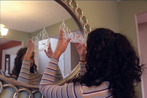 Abi Meyyappan, National American Miss Indiana (NAMI) finalist and senior, adjusts her tiara in a mirror. Meyyappan said she enjoyed her first beauty pageant experience.