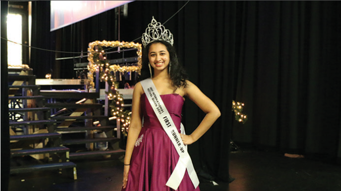 "STASH OF SASHES: Dressed in her pageant attire, Abi Meyyappan, National American Miss Indiana (NAMI) finalist and senior, poses for a picture on stage. Meyyappan said she thinks the pageant atmosphere is very supportive.Meyyappan said, ""You go out there, you put a smile on your face and you be proud of who you are because confidence makes anything look good."""