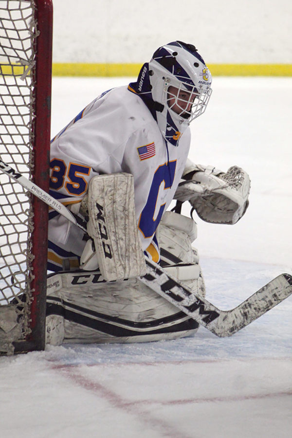 BACKSTOP: Nicholas Weninger, goalie on the Carmel Icehounds Blue team and freshman, prepares to make a save. Weninger said the low number of students attending Icehounds games to the teams results not being announced on the announcements like all varsity sports are.
