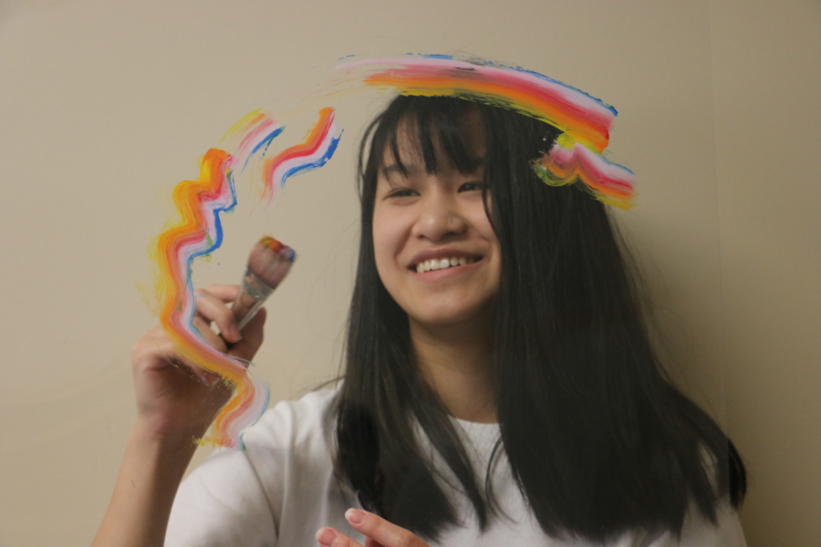 Junior Shannon Xie paints on a sheet of plastic hung from the ceiling. She said she likes doing both digital and traditional painting, with her traditional art pieces being mainly oil and acrylic paintings.