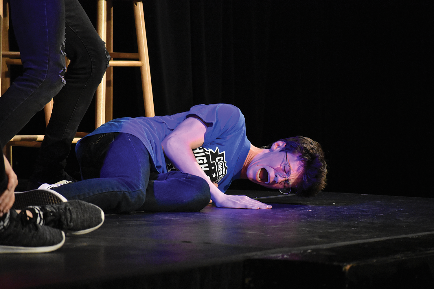 ON THE FLOOR: Junior Austin Audia performs during a ComedySportz match after school. Members often incorporate unique styles of humor to win ComedySportz matches.