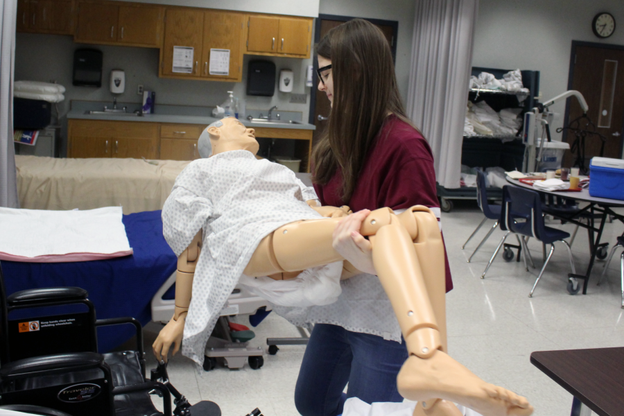 Cassidy Bruner, JEL student and senior,  spends time pretending to  moving a patient into a wheelchair with a mannequin. JEL students get time to apply their learnings outside of class, whether that is as an intern, or when visiting hospitals and other locations that work with JEL.