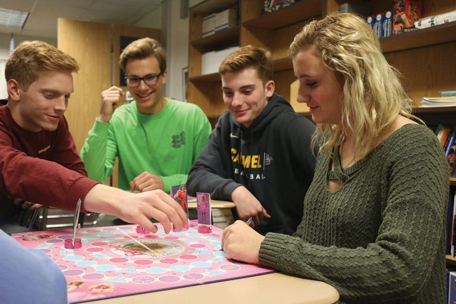 GAME PLAY: Seniors Brandon Teater, Gabe Quigley, Michael Uhrig and Cassidy Eckstein (left to right) play a board game that they play with their mentees during the K-8 Mentor SRT. Eckstein said the mentor experience has humbled her and opened her eyes to the struggles those around her face.