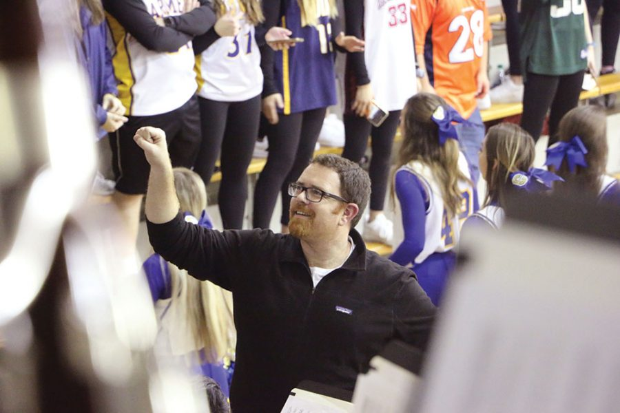 Kyle Young, associate director of bands, directs the pep band at a varsity boys' basketball game. Young said the band helps to create a unique form of encouragement at sports games.