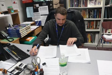 Club sponsor James Ziegler looks over assignments after class. According to Ziegler, the club has a busy season ahead of them as the primary and presidential elections approach.