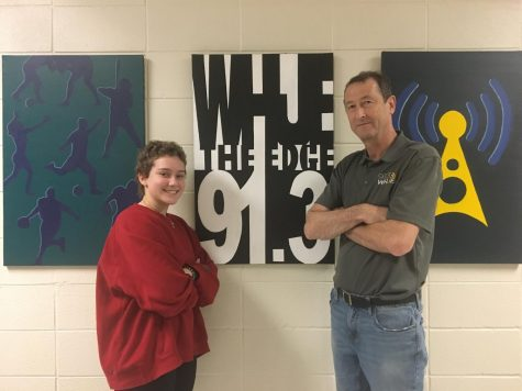 Junior Jess Cooper and radio adviser Dominic James stand by the WHJE sign. Cooper said WHJE will partner with Cabinet to raise money for Riley.