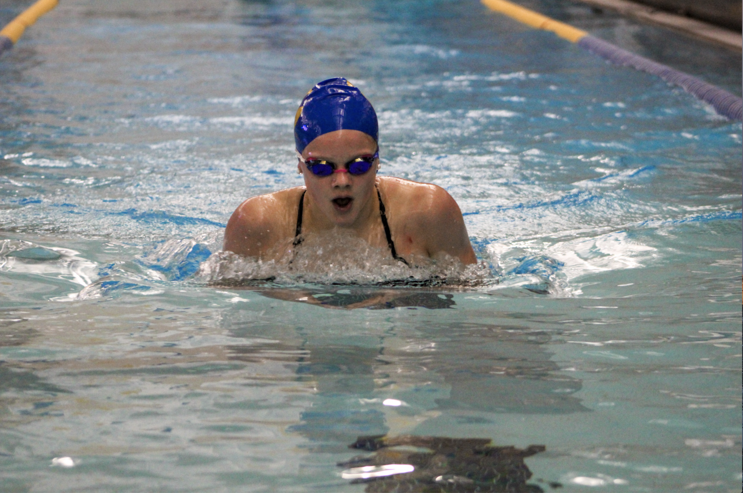 BREAST STROKE: Swimmer and freshman Berit Berglund, swims breastroke at the Carmel- HSE dual meet on Dec. 17. Berglund said despite having experience swimming with Carmel Swim Club in previous years, she has felt new pressures since joining the women's swimming team as a freshman. She added that the high school team is more competitive and serious than she experienced in the Carmel Swim Club.
